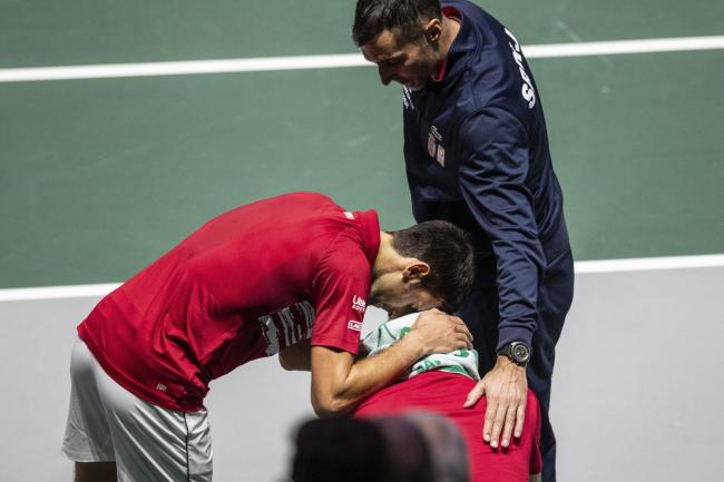 Novak Djokovic, left, and captain Nenad Zimonjic, right, comfort Viktor Troicki