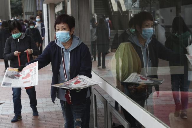 A woman wearing a protective face mask delivers a leaflet on coronavirus in Wuhan