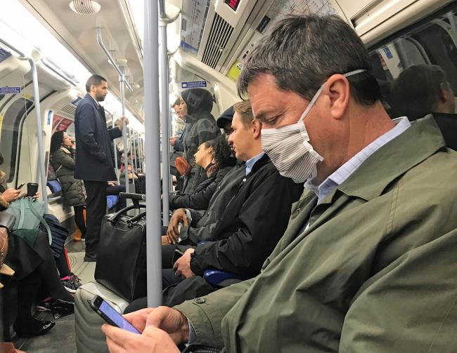 A man on the Jubilee line of the London Underground tube network wearing a protective facemask on the day that Heath Secretary Matt Hancock said that the number of people diagnosed with coronavirus in the UK has risen to 51. PA Photo. Picture date: Tuesda