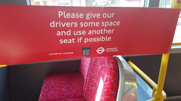 Tottenham Independent: Signs on buses ask passengers to sit away from the driver.