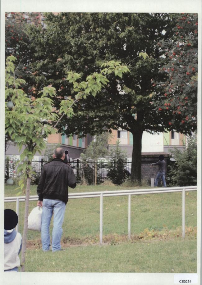The police firearms commander can be seen standing under the tree with his arm outstretched pointing to where he claims to have found the gun
