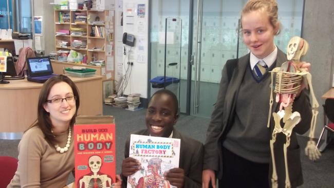 Ms H Swinyard, with Year 9 pupils Michael Antwi and Sarah Hempting help pick the winning book